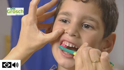 Adulto ensinando a escovar os dentes de uma criança corretamente